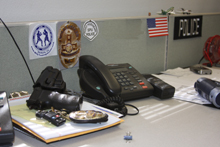 Gun, badge, and phone on detective desk