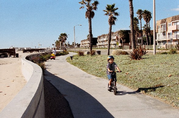 Boy riding bike beside beach